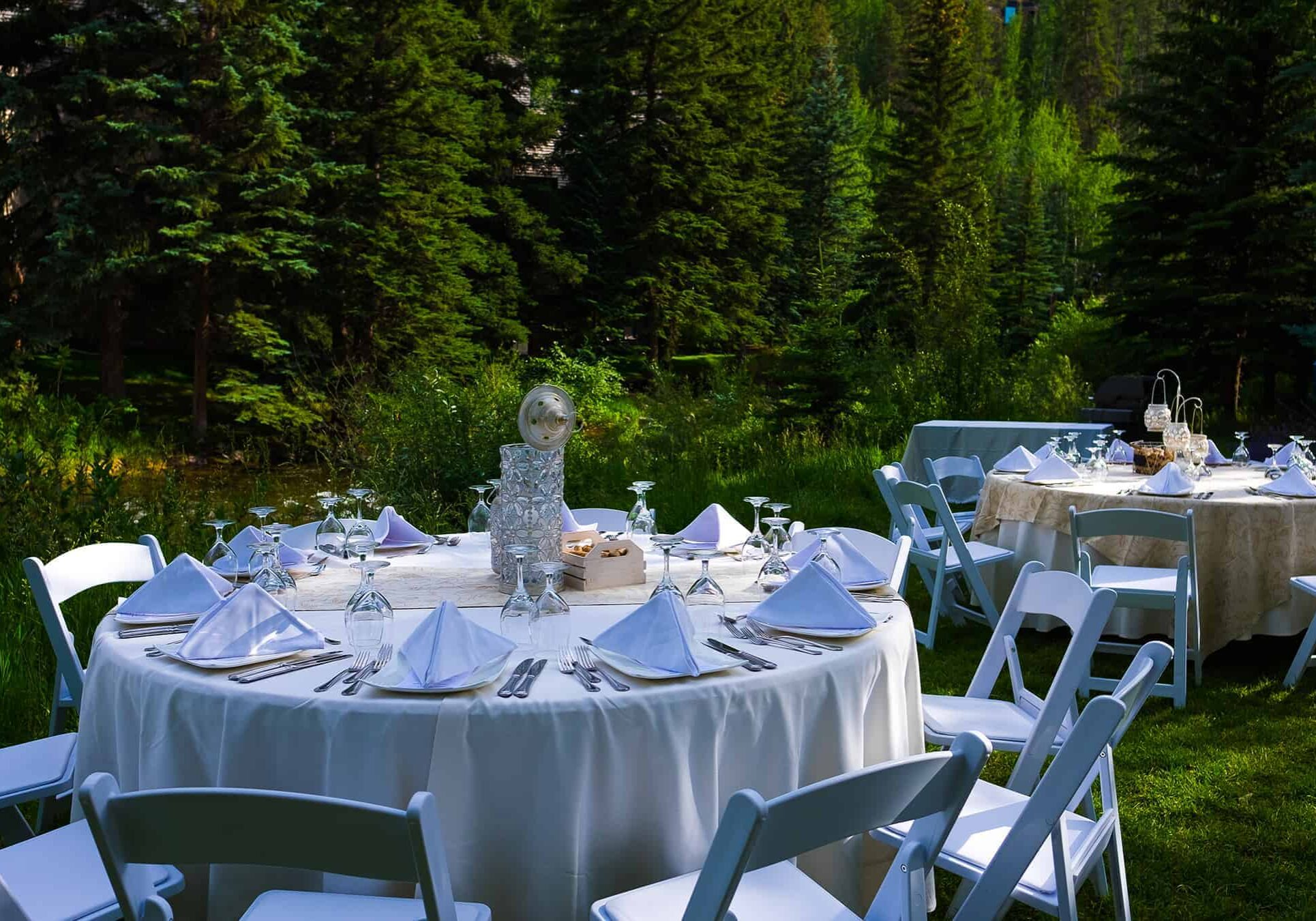 Reception tables outdoors, on grass, with placesettings