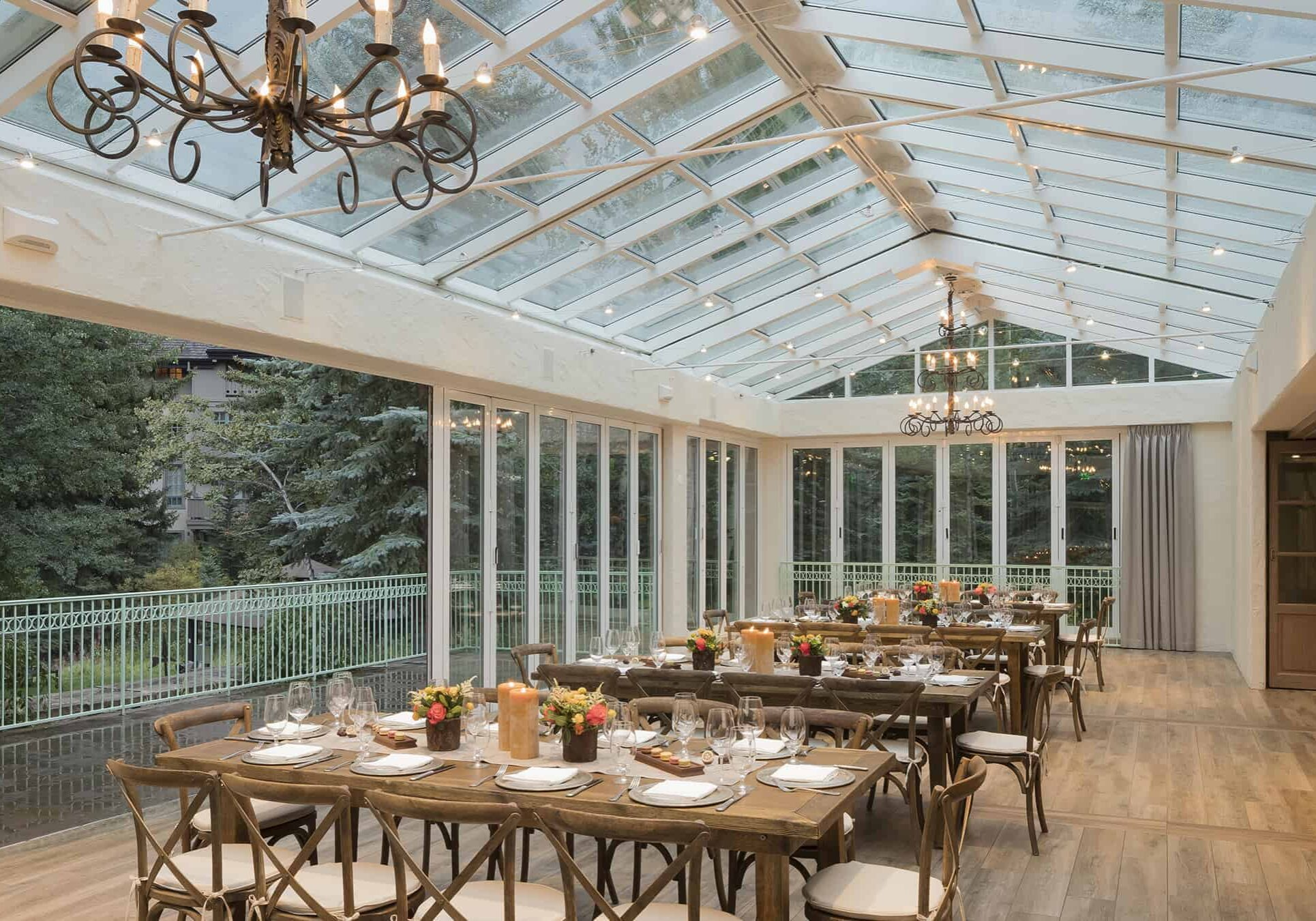 Outdoor terrace with glass roof, and tables wth placesettings