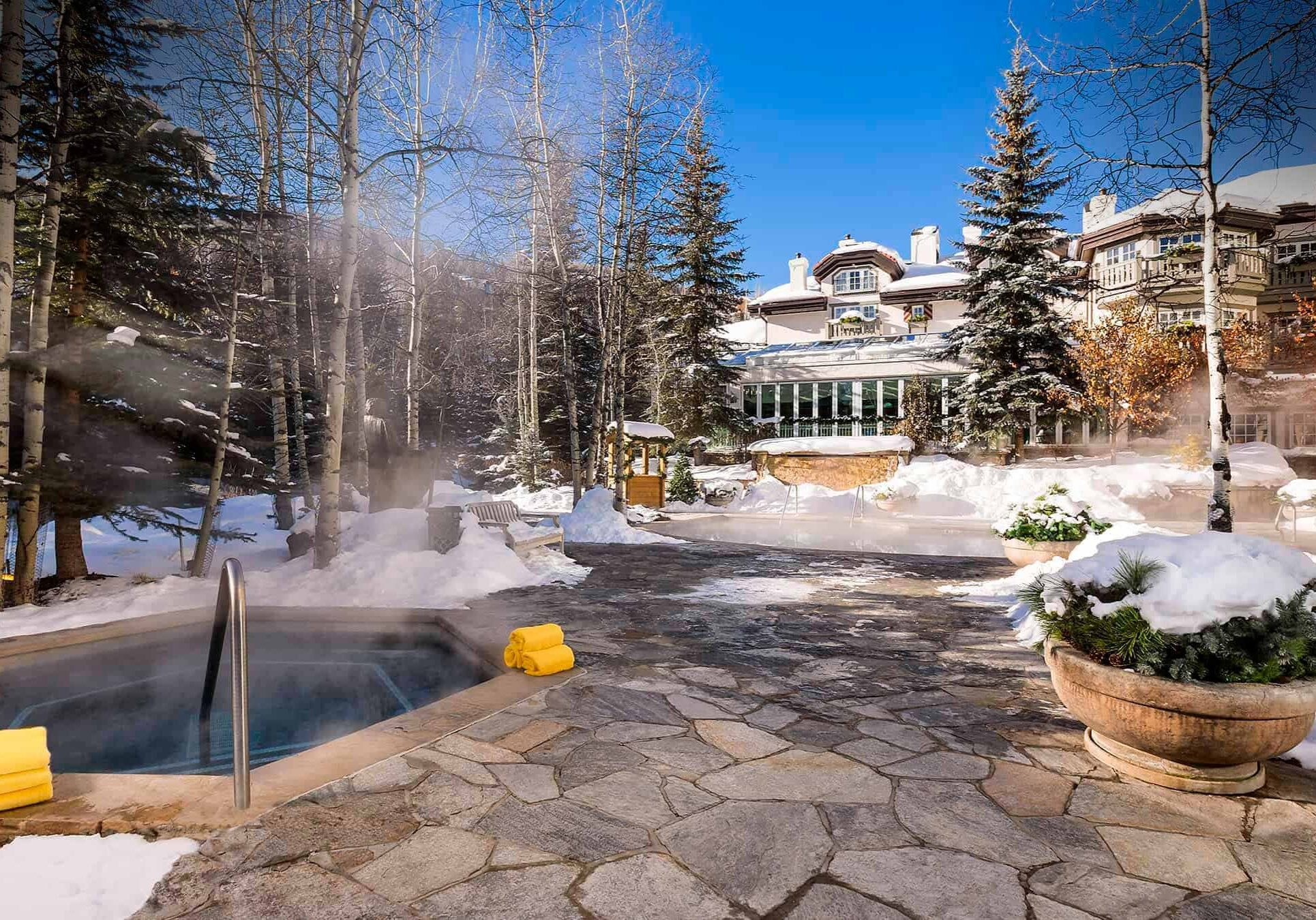 Steam rises from hot tub on a sunny day, as snow covers the ground and spa building is visible in the background