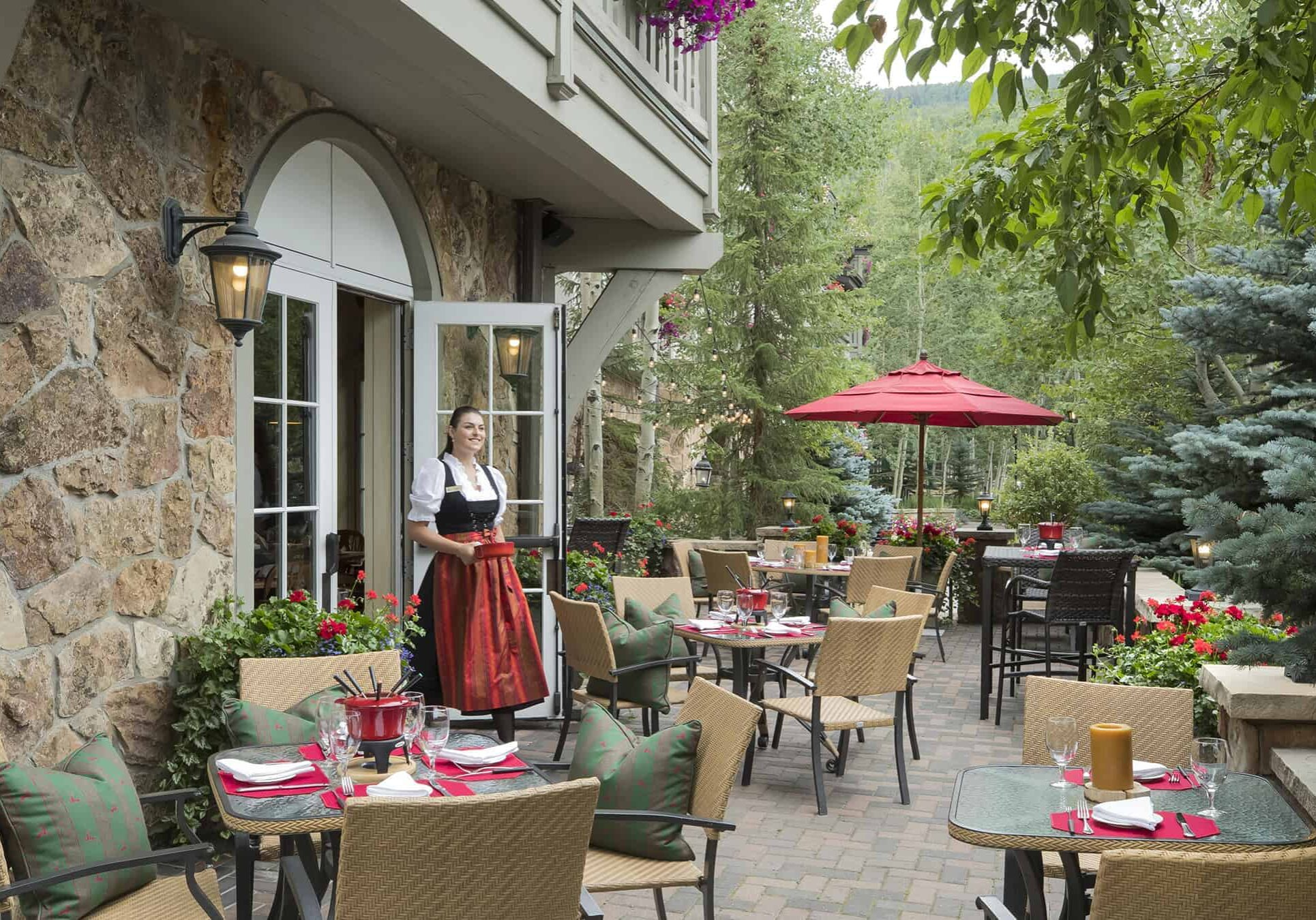 Sonnenalp Swiss Chalet outdoor patio with tables, chairs, and woman wearing dirndl carrying pot