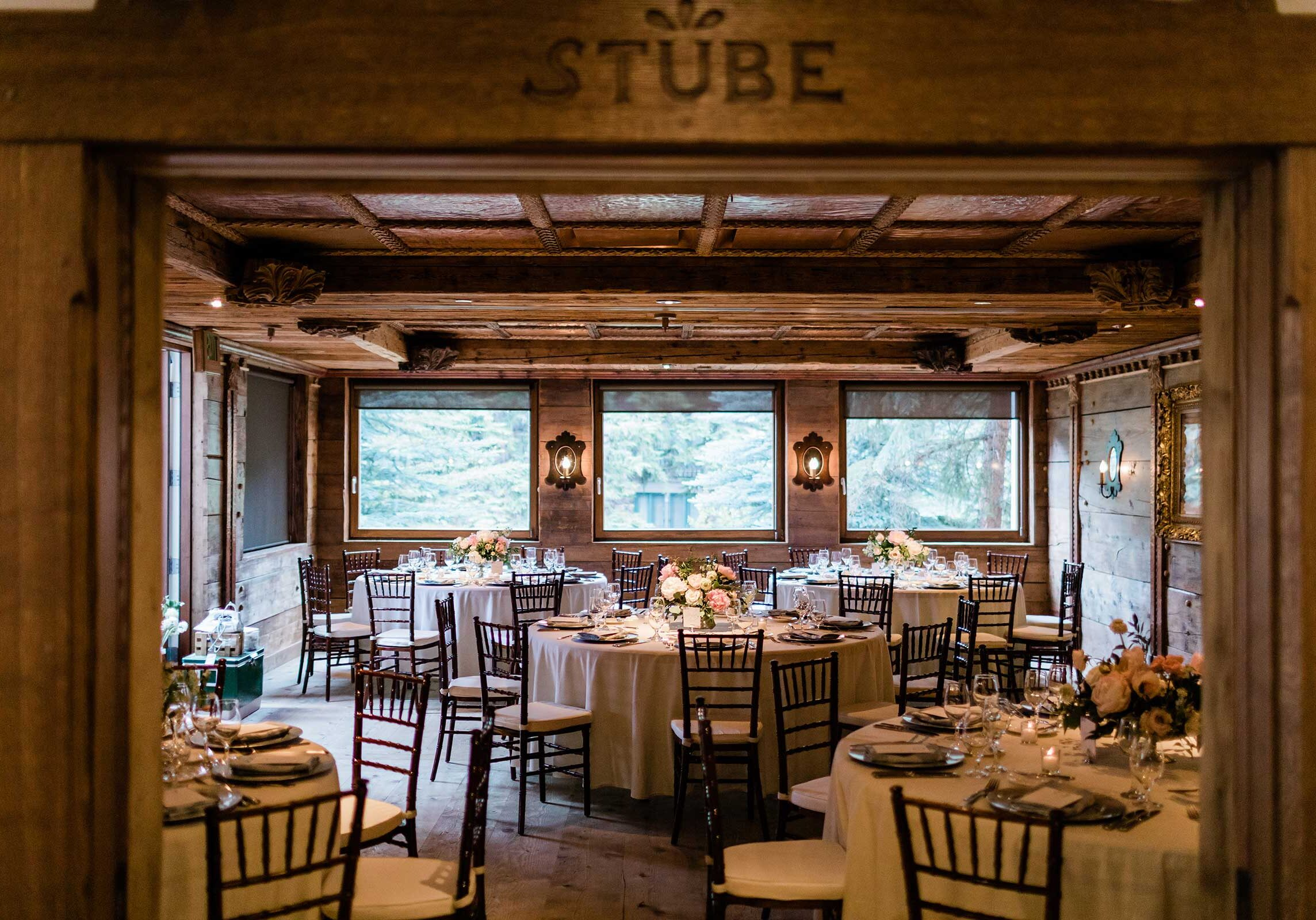 Room with wooden walls, and tables with centerpieces and placesettings