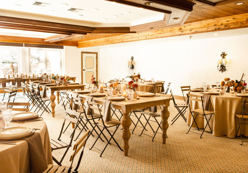 Carpeted room with tables with centerpieces and placesettings