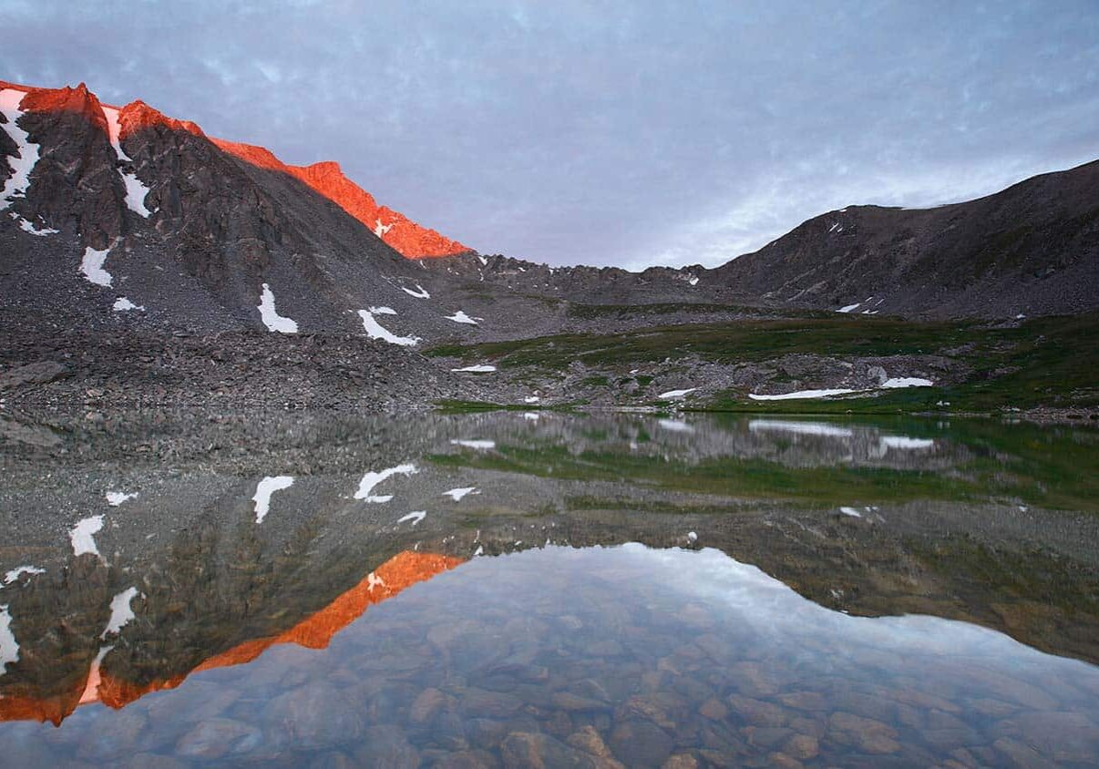 Mountain peaks at sunset reflected on shallow body of water