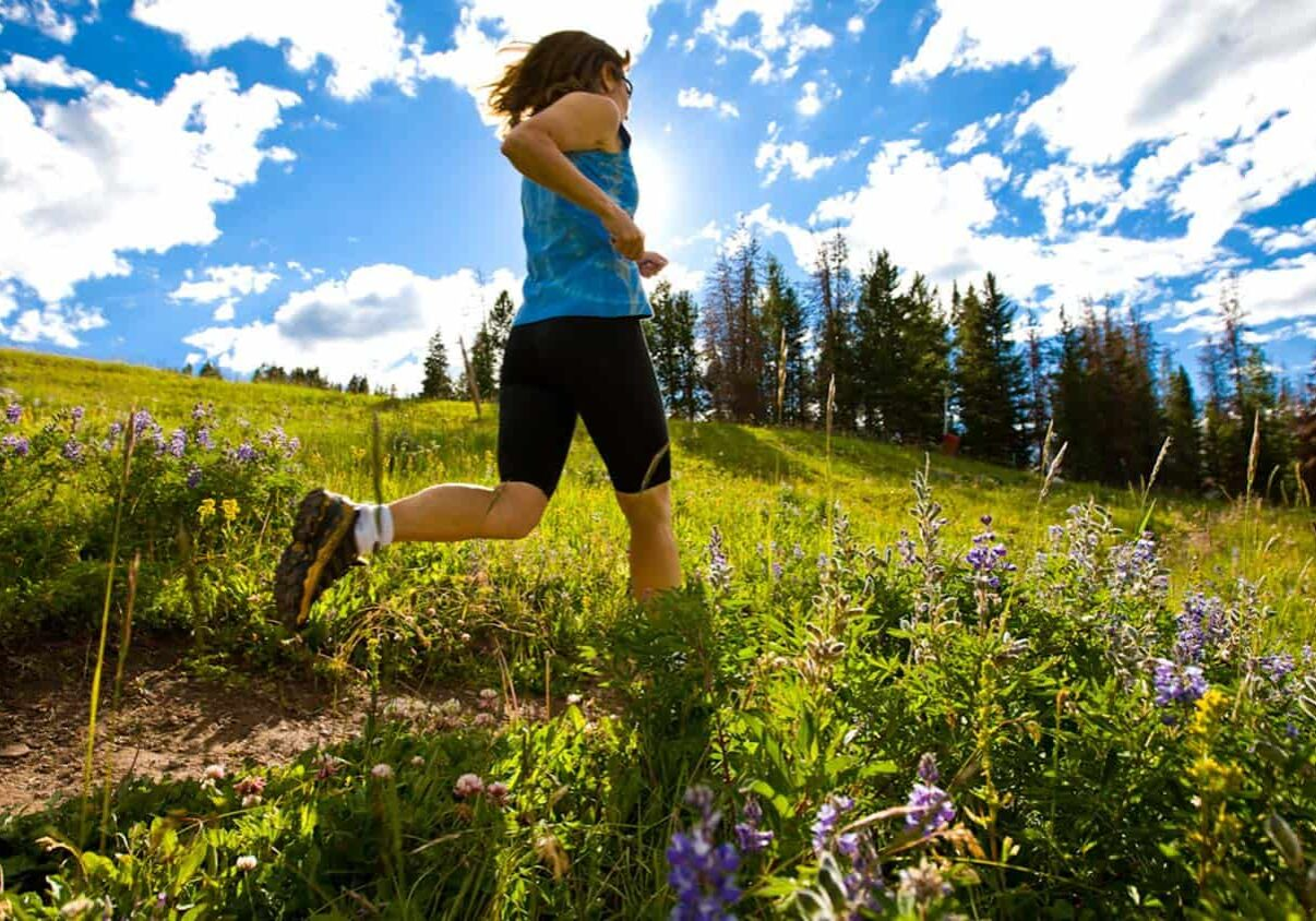 Woman wearing hiking boots, running through a field on a sunny day