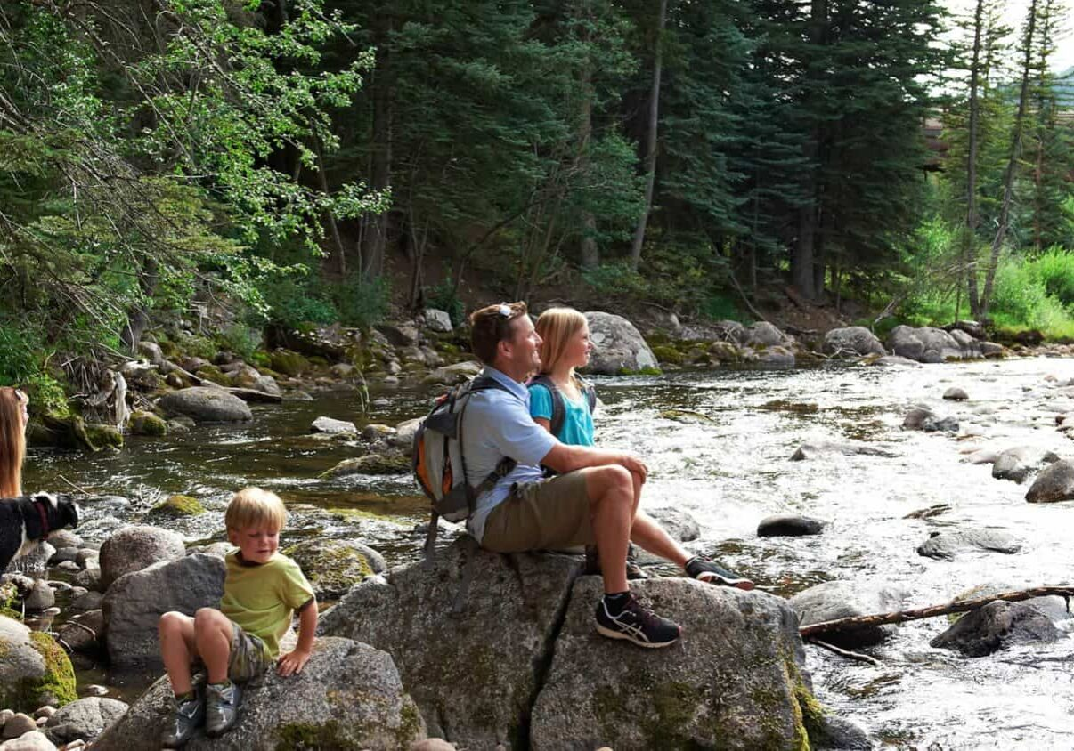family with dog sitting on rocks on the bank of a creek