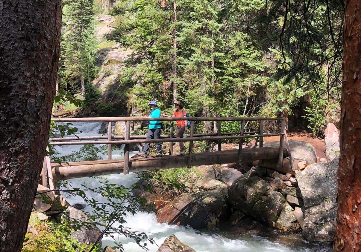 Two people crossing wooden bridge on foot over river stream