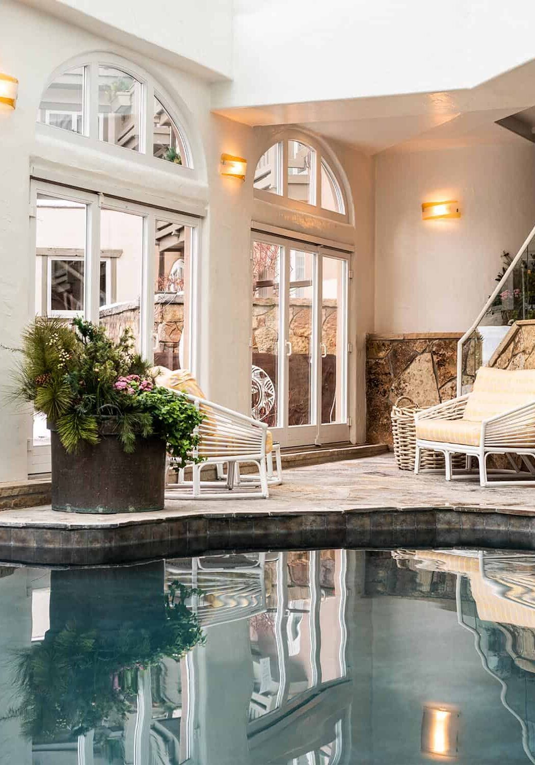 Indoor pool area with patio furniture and large glass doors leading to an outdoor area