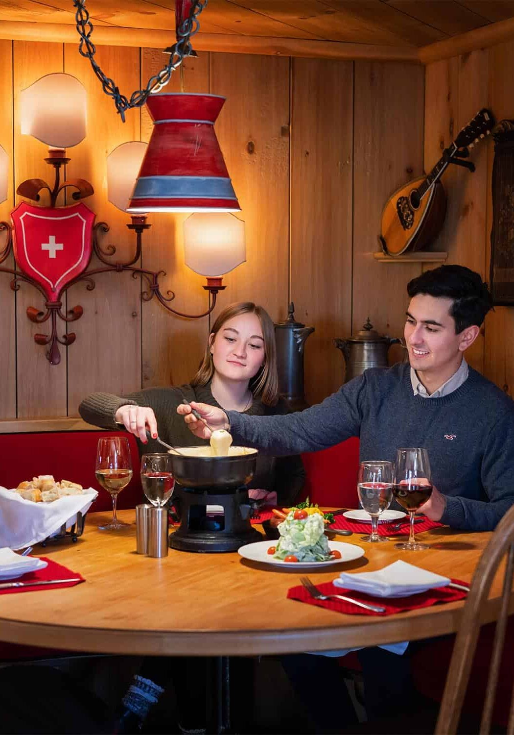 Couple seated at table, eating fondue