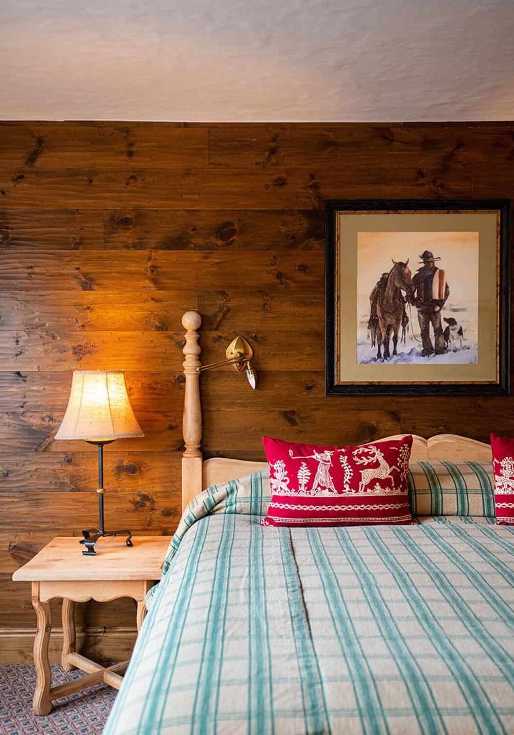 Hotel bed with carpeted floor, wood-paneled wall with art, and nightstand with small lamp