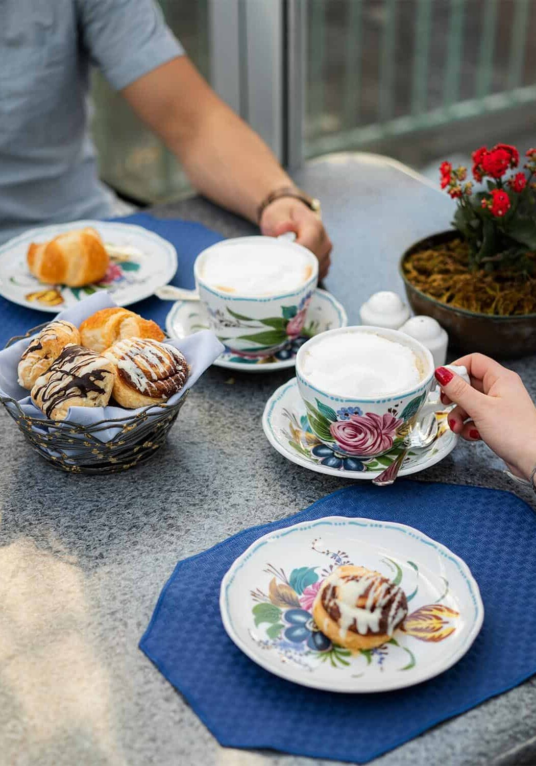 Closeup of table with breakfast pastries, and two people holding coffee cups